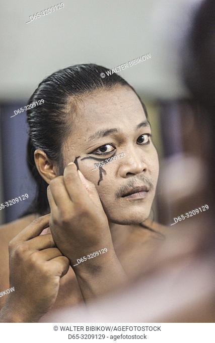 Cambodia, Battambang, Phar Ponleu Selpak, arts and circus school, young acrobat applying makeup before circus performance, ER