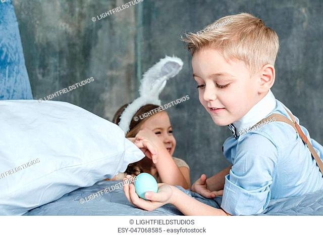 Cute smiling boy holding painted easter egg near smiling little sister in bunny ears