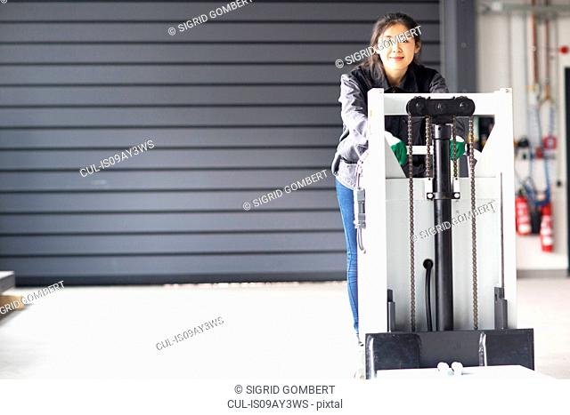 Technician moving machine in factory