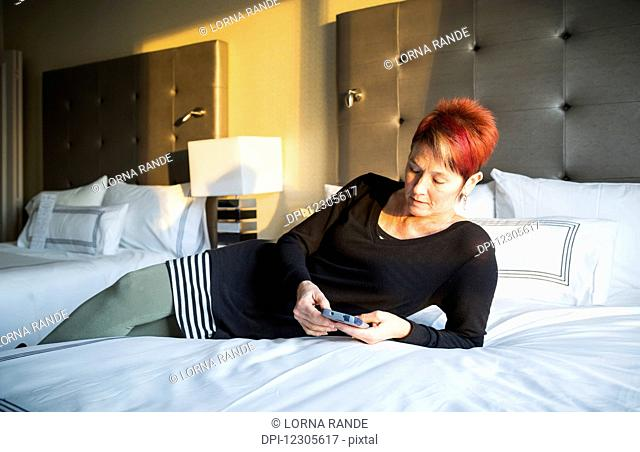 A woman laying on a hotel bed and texting; Vancouver, British Columbia, Canada