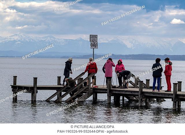 26 March 2019, Bavaria, Possenhofen: Nine hikers from the Starnberg Kneipp Association stand on the Steg1 on the shores of Lake Starnberg near Possenhofen and...
