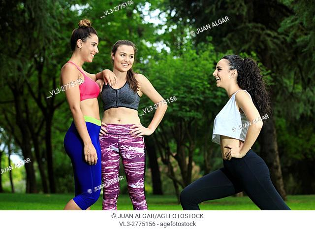 Three girlfriends having fun while exercising in park