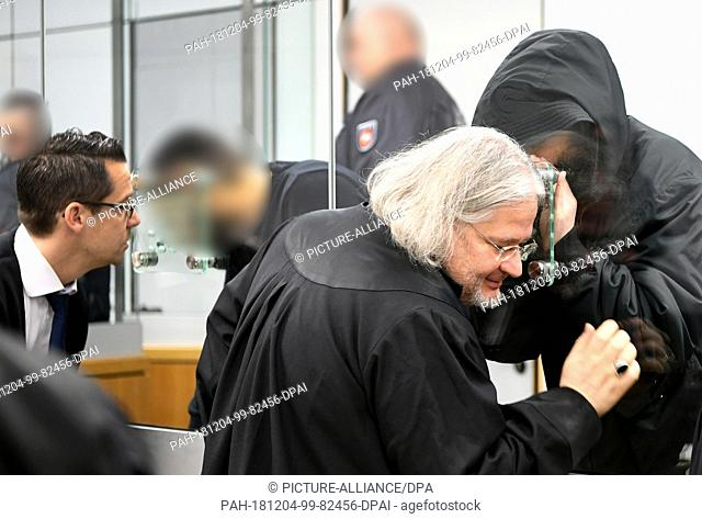 04 December 2018, Lower Saxony, Celle: A defendant talks to his defender Michael Murat Sertsöz (2nd from right). On the left