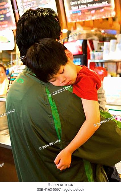USA, WASHINGTON STATE, SEATTLE, PIKE PLACE MARKET, TIRED ASIAN BOY SLEEPING ON SHOULDER OF FATHER