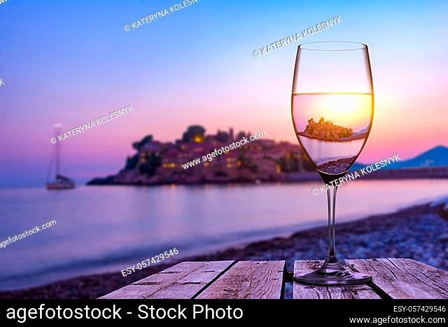 Wineglass on old wooden table on the beach of Sveti Stefan at sunset, Montenegro