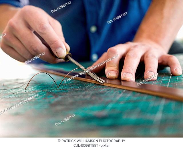 Leatherworker trimming leather for handbag strap in workshop, close up of hands