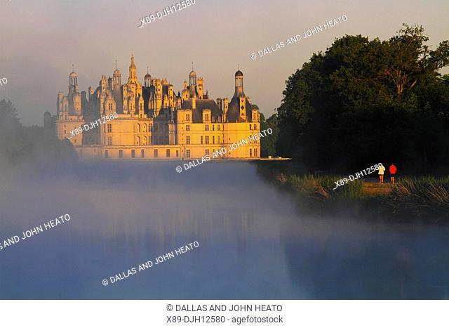 France, Loire Valley, Loir-et-Cher, Chambord, Château de Chambord, Men Jogging in the Park in early morning fog