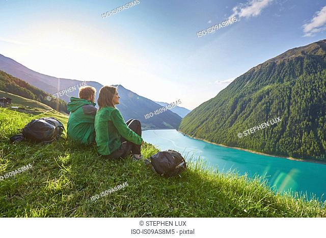 Young couple sitting looking out over Vernagt reservoir and Finailhof farmhouse, Val Senales, South Tyrol, Italy