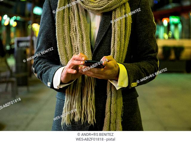 Close-up of man using his cell phone in the city at night