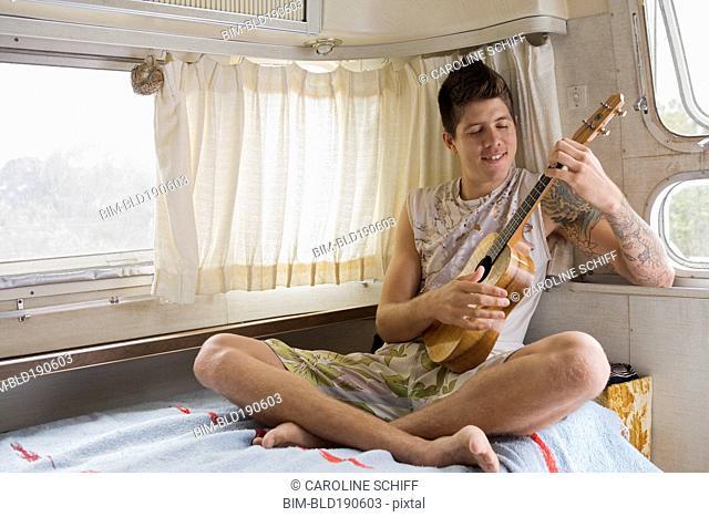 Mixed race man playing ukulele