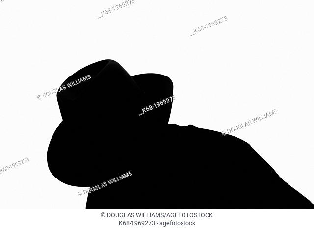 silhouette of a middle-aged man, head and shoulders, looking down, wearing a fedora