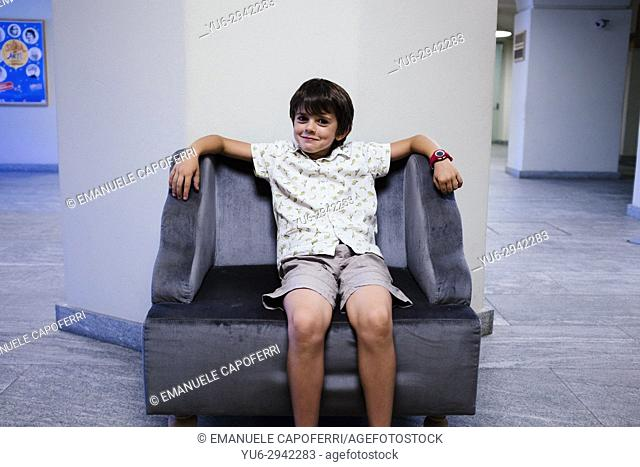 Young boy sitting on an armchair