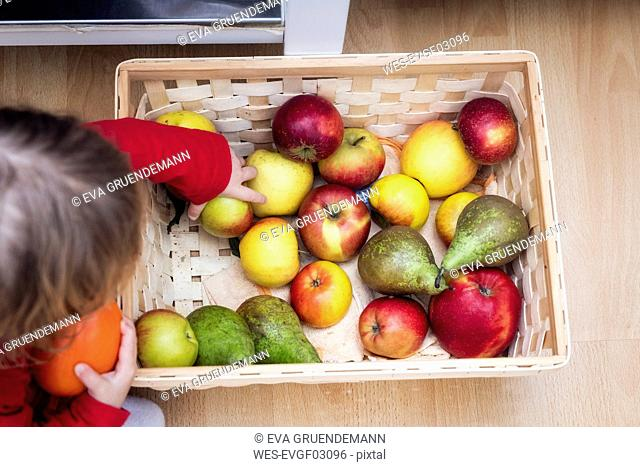 Little girl taking apple, top view