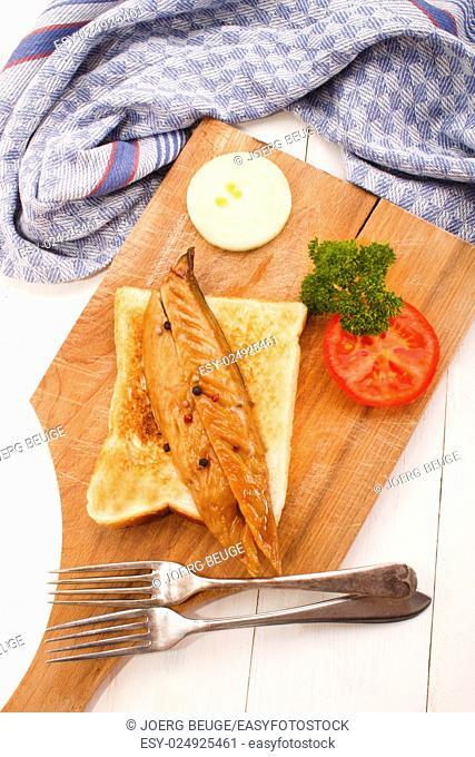 fresh smoked scottish mackerel on sliced bread with tomato, parsley and onion