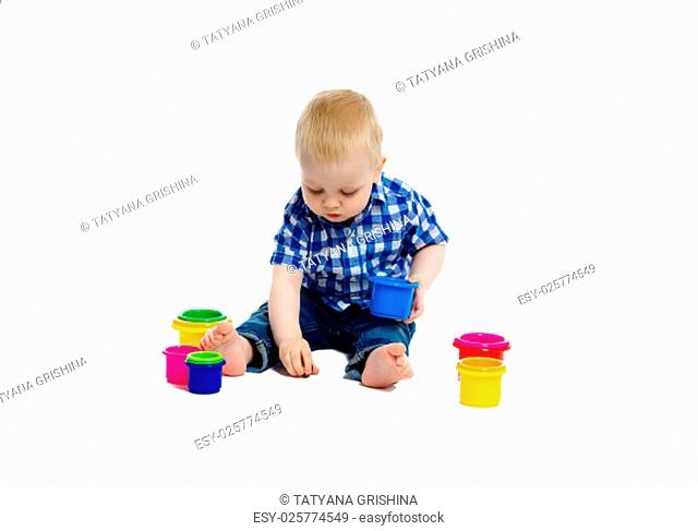 A little boy in checkered shirt plays on the floor. White background. Studio