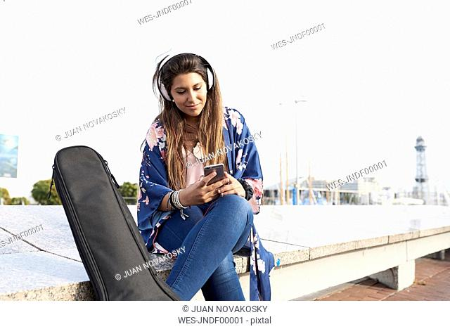 Spain, Barcelona, portrait of woman with guitar case and headphones looking at cell phone