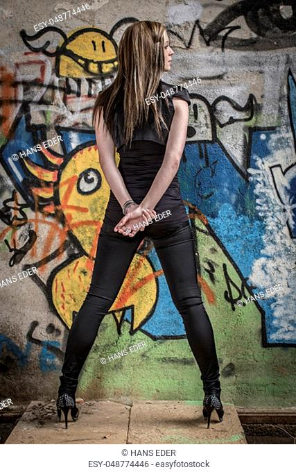 Young woman with leggings and mini dress post in front of graffiti paintings