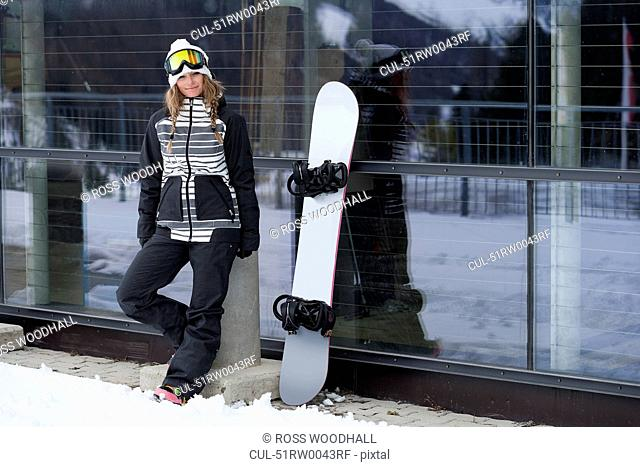 Snowboarder standing by lodge
