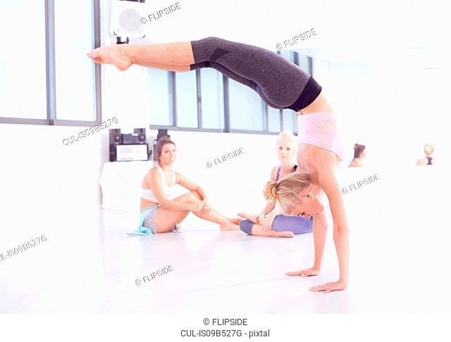 Young female ballet dancer practicing in dance studio, doing handstand
