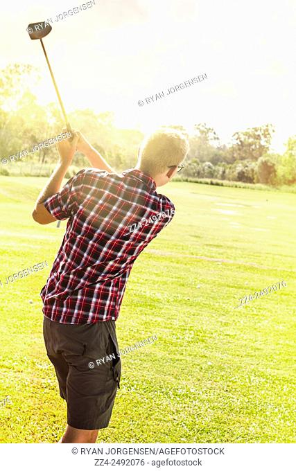 Exercise and sport photo of a young golf player on course practising swing on tee off. Golfing in Australia