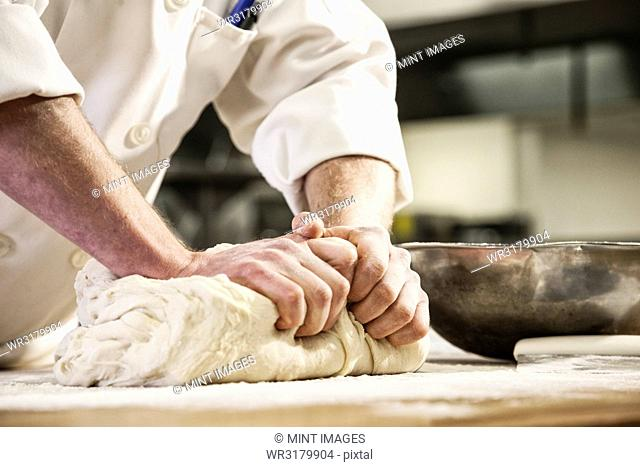 A chef's hands kneading bread dough on a floured worktop