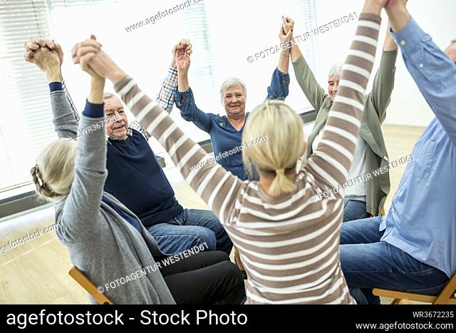 Group of seniors practicing chair gymnastics with instructor in retirement home