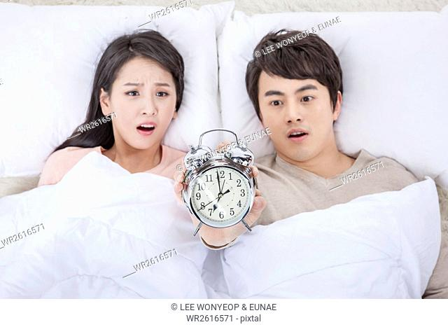 Portrait of young couple with alarm clock