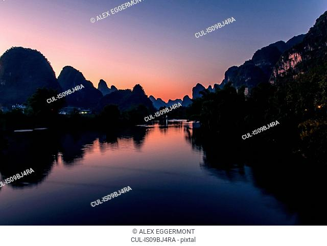 Sunset over river and Guilin Sugarloaf, Yangshuo, Guangxi, China