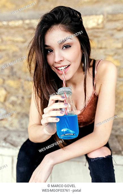 Portrait of a smiling brunette woman drinking blue lemonade