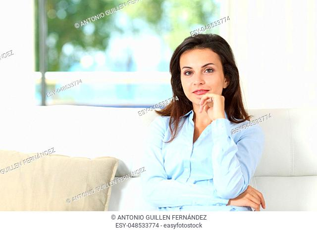Smiley confident housewife looking at camera sitting on a couch in the living room at home
