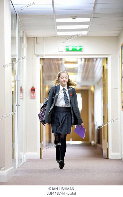 Portrait middle school student walking in school corridor
