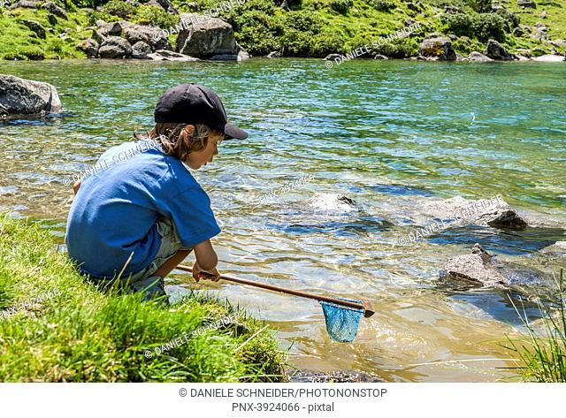 France, Pyrenees National Park, Val d'Azun, 6-year-old boy fishing by the Suyen lake on the gave d'Arrens (name referring to torrential rivers