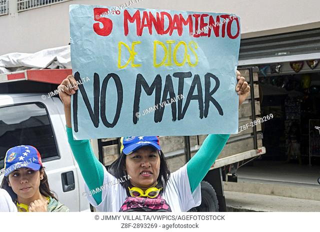 A woman with a sign that says: 5th Commandment of God . . . Do not Kill. In the protest of the opposition. The opposition made this Monday, June 19