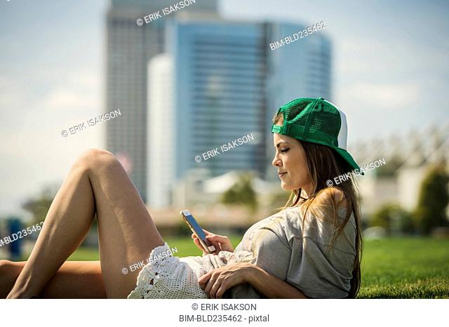 Caucasian woman laying in grass texting on cell phone