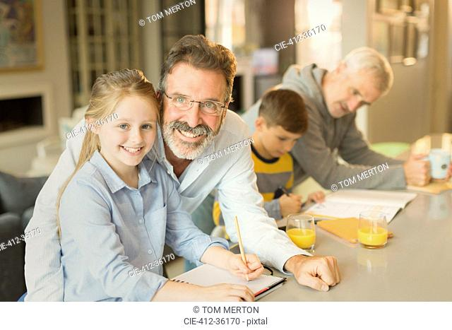 Portrait male gay parents helping children with homework at kitchen counter