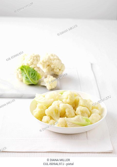 Raw cauliflower on marble cutting board and bowl of boiled cauliflower