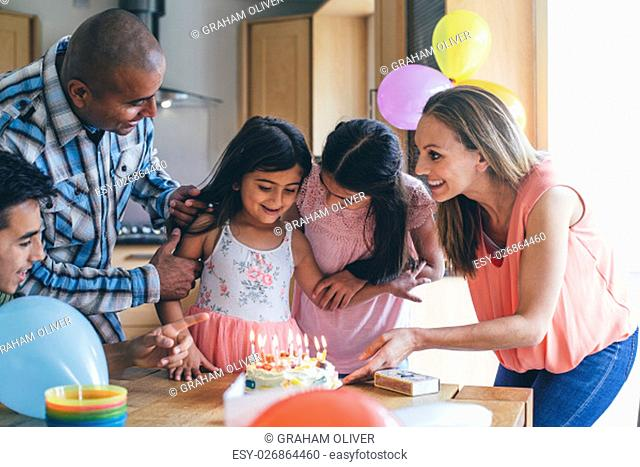 Happy family celebrating the youngest girls birthday with cake at home. They are singing to her before she blows out the candles