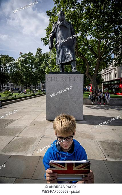UK, London, boy standing in front memorial for Winston Churchill taking a selfie with his digital tablet
