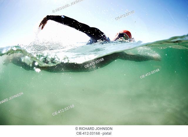 Male swimmer triathlete swimming in ocean