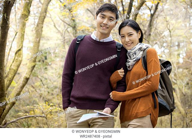 Young smiling couple trekkers arm in arm in forest in fall