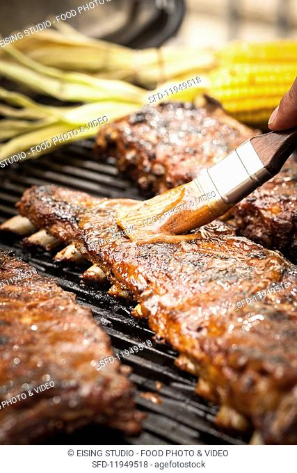 Spare ribs being brushed with a spicy marinade