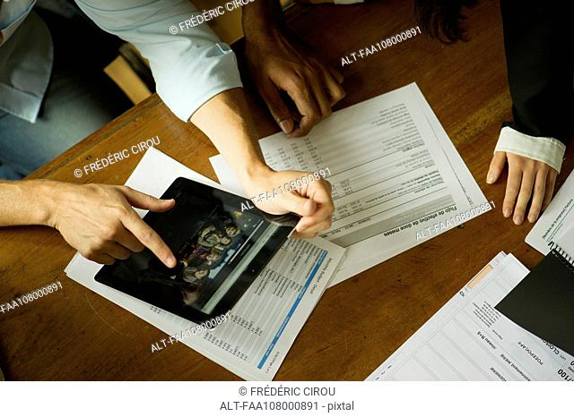Colleagues using digital tablet during meeting