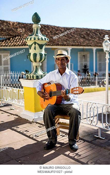Cuba, Trinidad, man playing guitar on the street