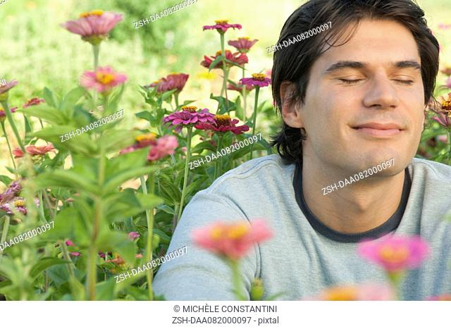Mid-adult man in zinnia flowers with eyes closed, smiling
