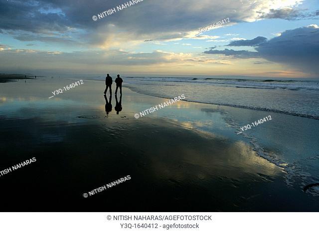 A leisurely walk at dusk along the beach in San Francisco, California, USA