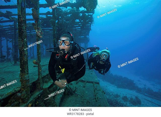 Two divers swimming along the remaining structure of a shipwreck