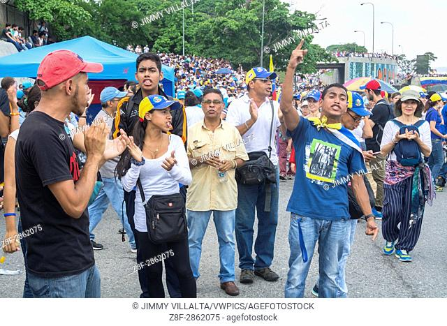 A group of young people shout slogans for the release of political prisoners, in protest of the opposition on a main highway in Caracas on Monday, April 24th
