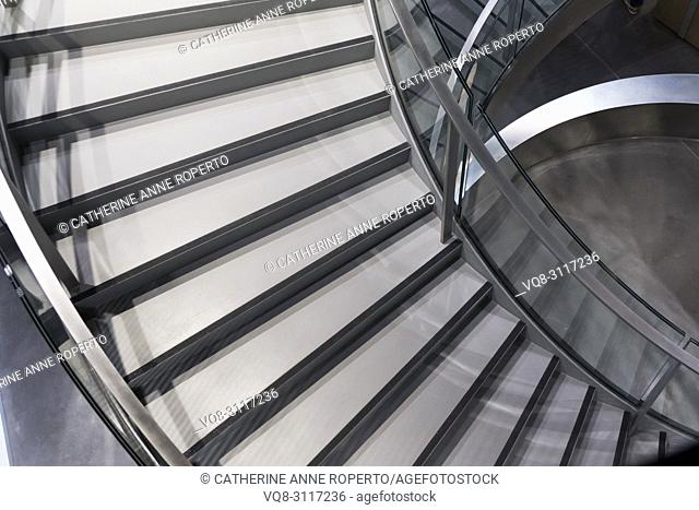 Dramatic geometric circling staircase reflections in chrome and glass at the Roman Museum in Nimes, Provence, France
