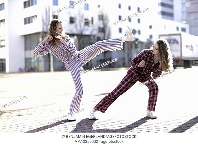 young women fighting at street, wearing pyjamas