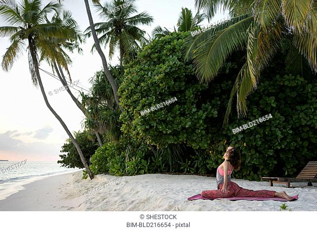 Caucasian woman practicing yoga on tropical beach